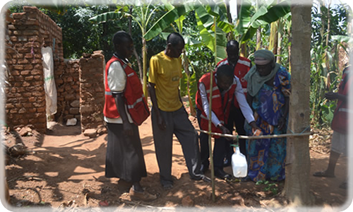 Red Cross Volunteers setting up a tippy tap at Jalia's home